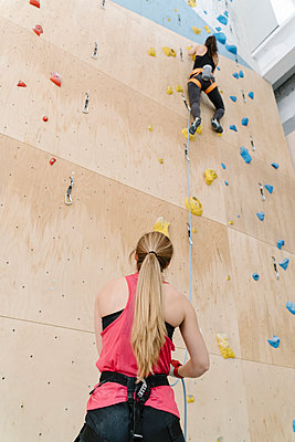 Woman with a rope securing partner on the wall in climbing gym - p300m2170344 by Hernandez and Sorokina