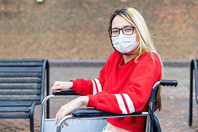 Disabled woman on wheelchair wearing face mask during coronavirus outbreak - p300m2207100 by William Perugini