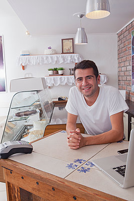 Smiling Hispanic baker leaning on counter - p555m1303362 by REB Images