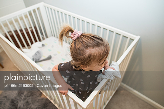 High angle of blonde toddler girl in crib bed. - p1166m2163008 by Cavan Images