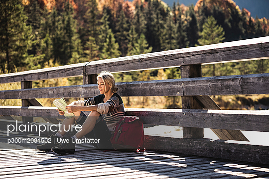 Austria, Alps, woman on a hiking  sitting on a bridge reading map - p300m2081502 by Uwe Umstätter