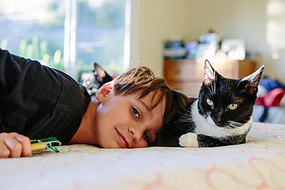 Portrait of boy and cat relaxing on bed at home - p1166m1403085 by Cavan Images
