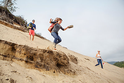 Woman jumping from sand dune while enjoying with friends at beach - p1166m1533996 by Cavan Images