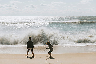 Brothers playing with waves at beach against sky during sunny day - p1166m2034778 by Cavan Images