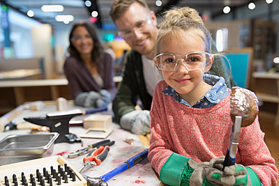Portrait daughter and parents playing with tools in science center workshop - p1192m1194266 by Hero Images