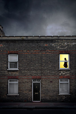 Silhouetted woman in a Brick Building - p1248m2200423 by miguel sobreira