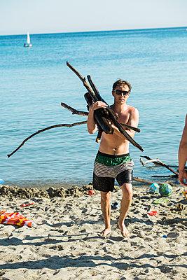 Junger Mann sammelt Feuerholz am Strand - p1437m2008196 von Achim Bunz