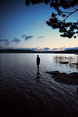 Silhouette of person at lake - p312m1192803 by Susanne Walstrom