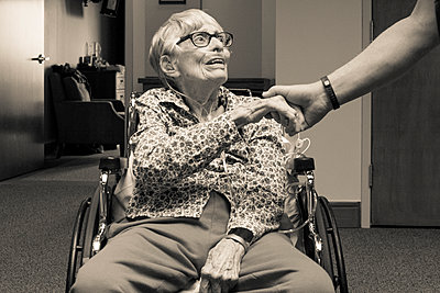 Senior woman in wheelchair shaking hand of man - p555m1409182 by Shestock
