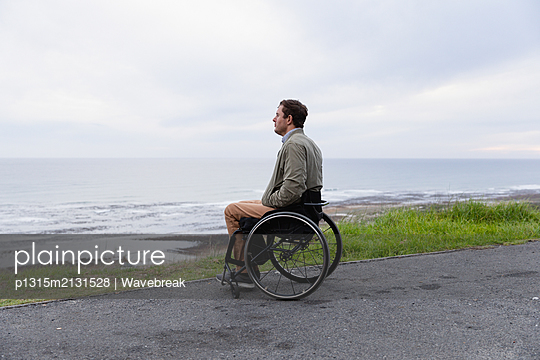 Disabled man in a wheelchair enjoying a day out - p1315m2131528 by Wavebreak