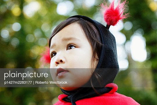 Young girl dressed up as ladybird - p1427m2283177 by Roberto Westbrook