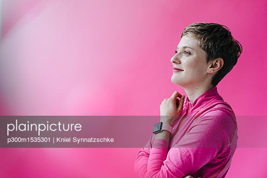 Woman in pink sportswear wearing smartwatch - p300m1535301 by Kniel Synnatzschke