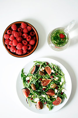 Overhead view of salad served in plate by raspberries and mint on table - p1166m1561223 by Cavan Images