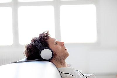 Junger Mann auf dem Sofa hört Musik mit geschlossenen Augen - p1212m1115994 von harry + lidy