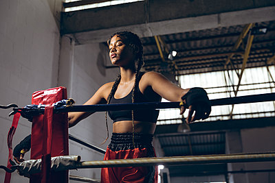 Female boxer with eyes closed leaning on ropes in boxing ring at boxing club - p1315m2130424 by Wavebreak
