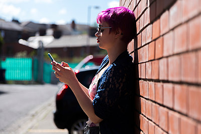 Young woman with dyed hair leaning against brick wall text messaging - p300m1166484 by Boy photography