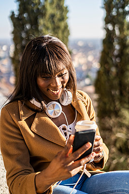 Smiling female tourist looking at her smartphone outdoors - p300m2139982 by Giorgio Fochesato
