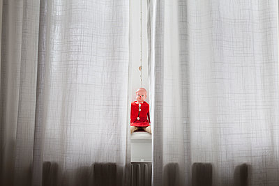 Doll sitting on windowsill behind curtains - p301m1406496 by Isabella Ståhl