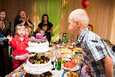 Caucasian boy blowing candles on birthday cake - p555m1410821 by Aleksander Rubtsov