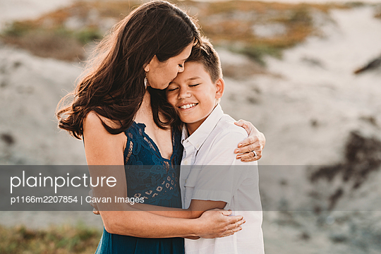 Loving mother embraces smiling preteen son - p1166m2207854 by Cavan Images