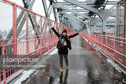 Woman cheering on Williamsburg Bridge, New York City - p1507m2196530 by Emma Grann