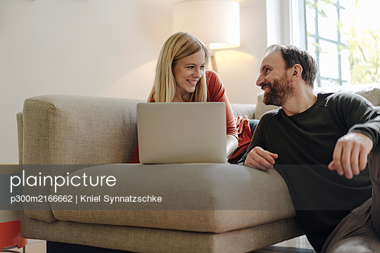 Couple sitting at home on couch, using laptop - p300m2166662 by Kniel Synnatzschke