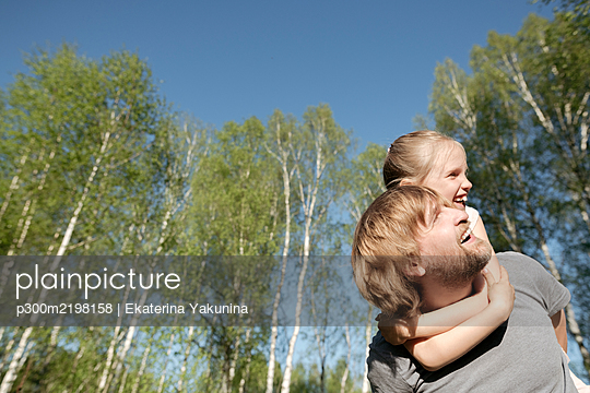 Happy father piggybacking daughter against trees in park during sunny day - p300m2198158 by Ekaterina Yakunina