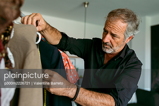 Mature male tailor measuring clothes on coathanger at work studio - p300m2226721 by Valentina Barreto