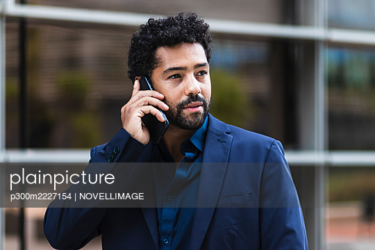 Businessman talking on mobile phone in city - p300m2227154 by NOVELLIMAGE