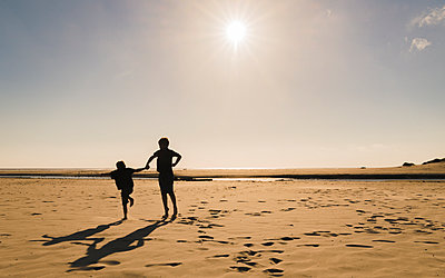 Silhouette brothers jumping at beach against sky during sunny day - p1166m1544970 by Cavan Social