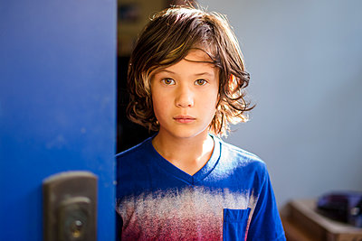 Portrait of serious boy standing by door against wall at home - p1166m2068087 by Cavan Images