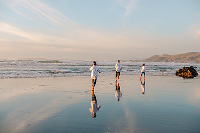 Rear view of three boys running over water during sunset - p1166m2073873 by Cavan Images