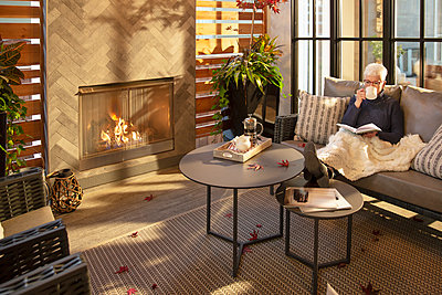 Senior woman relaxing, drinking coffee and reading book on living room sofa next to fireplace - p1192m2047669 by Hero Images