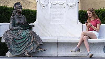 Teenager using smartphone alongside Sissi sculpture - p1376m2101483 by Melanie Haberkorn
