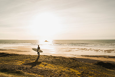 France, Bretagne, Finistere, Crozon peninsula, man standing at the coast at sunset with surfboard - p300m1120438f by Uwe Umstätter