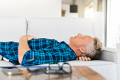 Casual man lying on couch relaxing - p300m2144668 by Steve Brookland