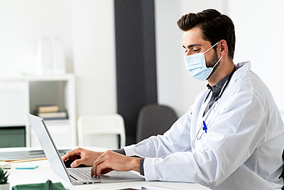 Male doctor wearing mask while using laptop at desk - p300m2275469 by Giorgio Fochesato