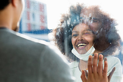 Smiling afro woman with face mask meeting male friend through glass wall - p300m2281686 by Emma Innocenti