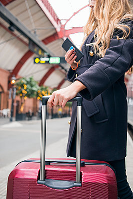 Woman holding suitcase handle - p312m2174867 by Viktor Holm