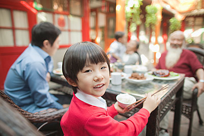 Chinese boy eating at table outdoors - p555m1464285 by Jade