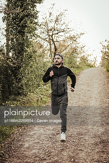 Man in cap and dark tracksuit running through the forest - p1166m2269594 by Cavan Images