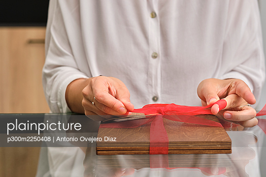Mid section of woman wrapping gift - p300m2250408 by Antonio Ovejero Diaz