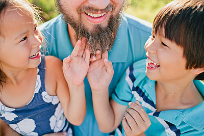 High angle view of siblings playing with father's beard - p1166m1182817 by Cavan Images