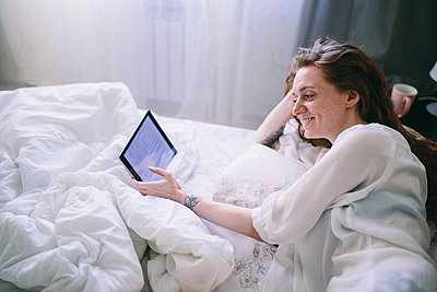 Young woman lies in bed and uses a tablet - p1363m1423676 by Valery Skurydin