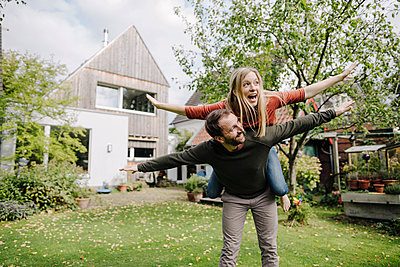 Cheering couple pretending to fly, standing in their garden - p300m2167273 by Kniel Synnatzschke