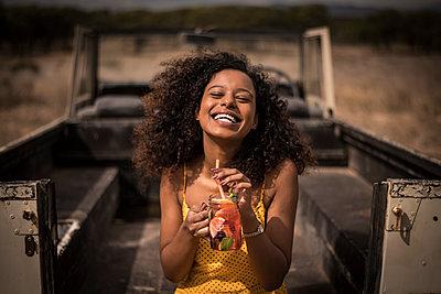 Portrait of laughing woman drinking fresh ice tea drink at safari bus - p300m2171217 by Malte Jäger