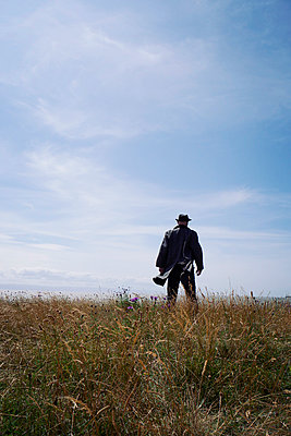 Man in hat and coat standing in meadow - p597m2108589 by Tim Robinson