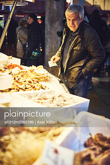 Man with banknote at a fish market with crustaceans - p1312m2082186 by Axel Killian