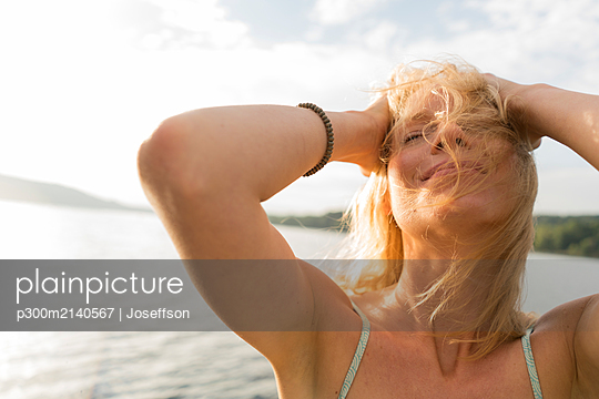 Young woman with windswept hair at a lake - p300m2140567 by Joseffson