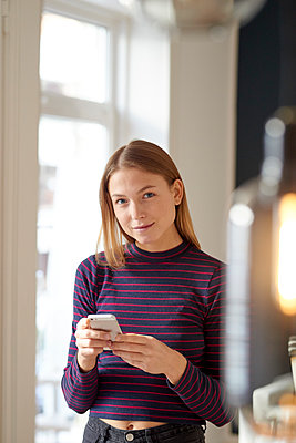 Young woman using smartphone - p1124m1589418 by Willing-Holtz